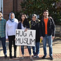 "five people holding ""Hug a Muslim"" sign"