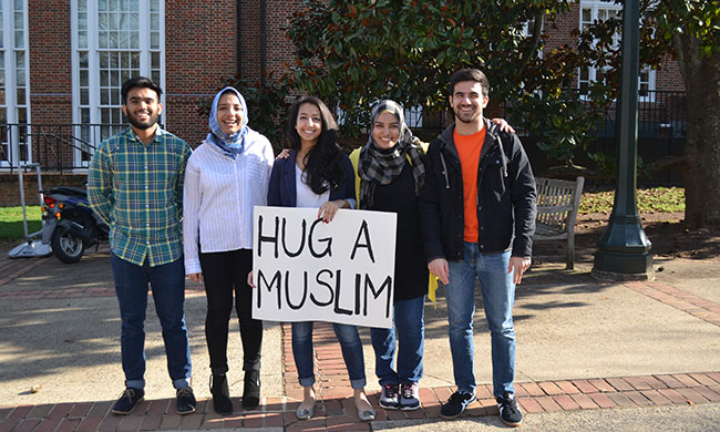 "five people holding ""Hug a Muslim"" sign"