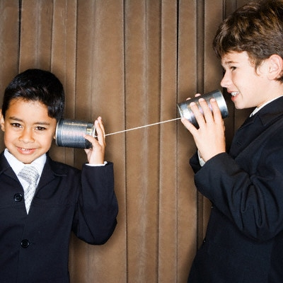 children talking with cans on string