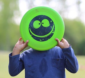 person holding frisbee with smiley face