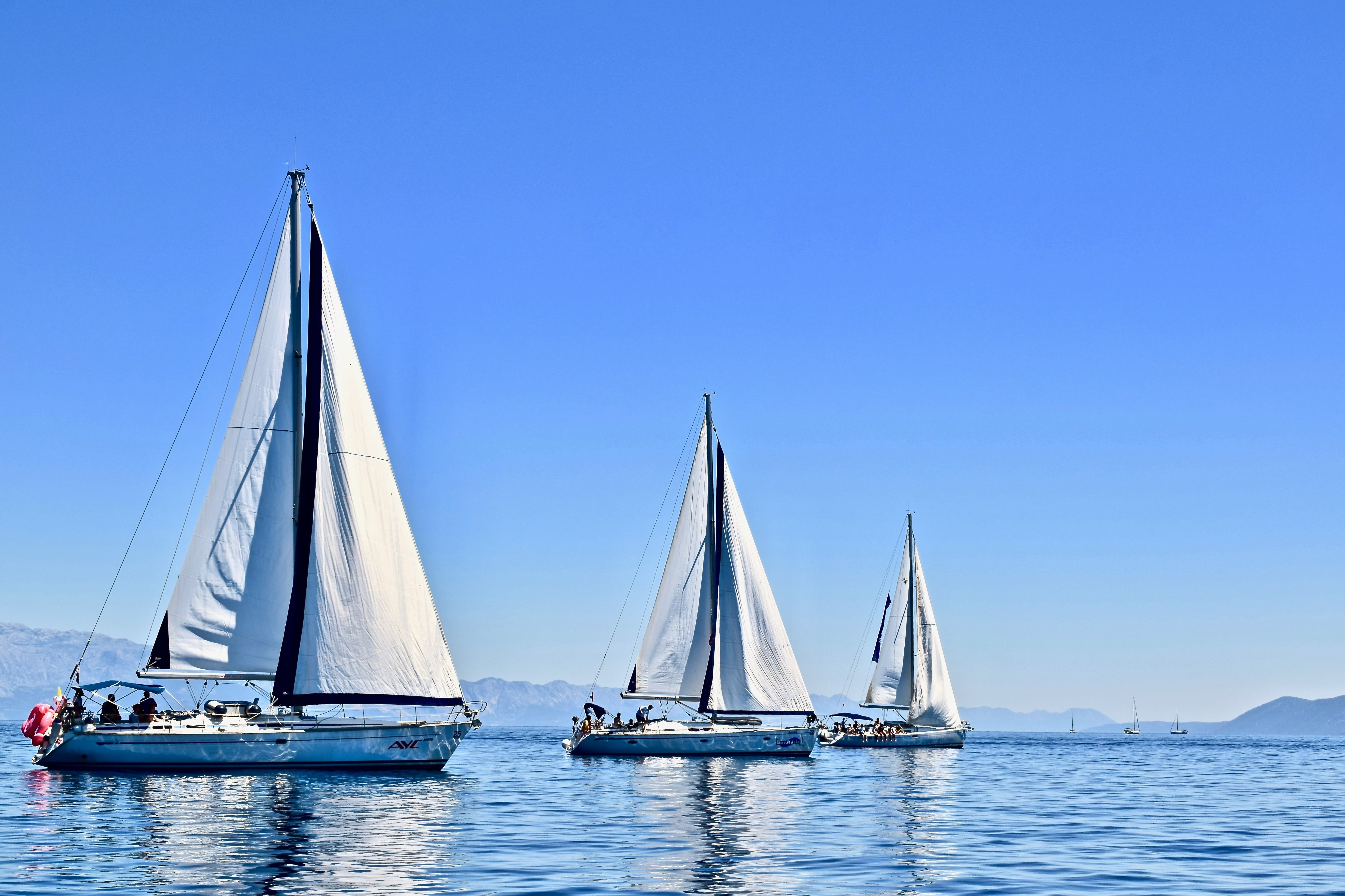 three sailboats on calm water