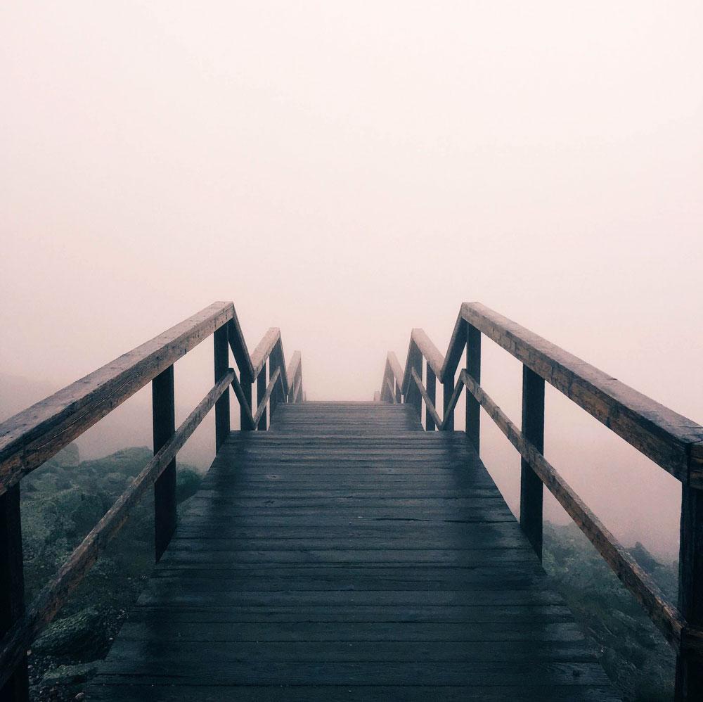 A bridge leads into a misty distance