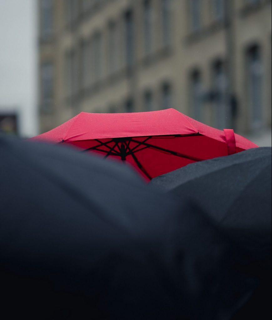 Red umbrella surrounded by black umbrellas