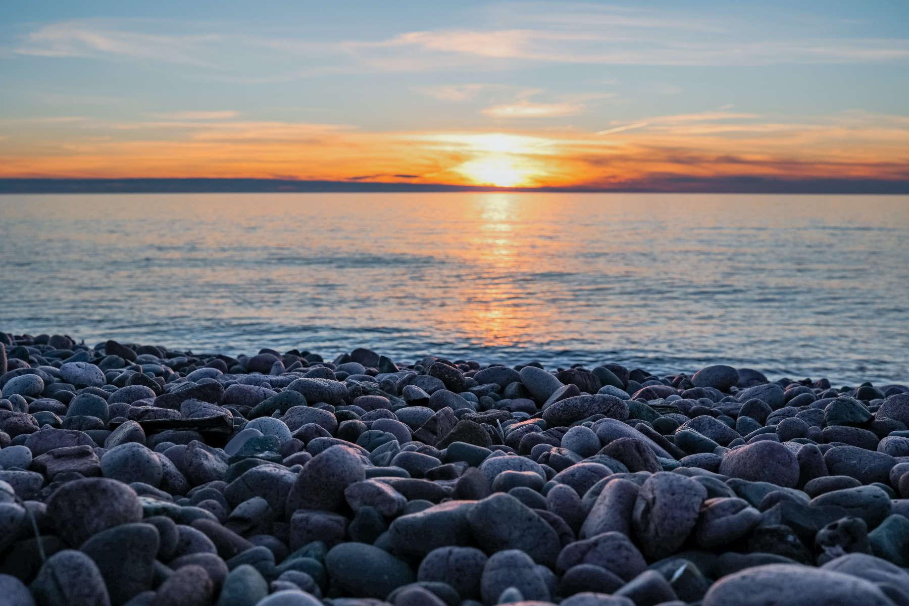 Sun sets on a placid lake, the coast is rocky.